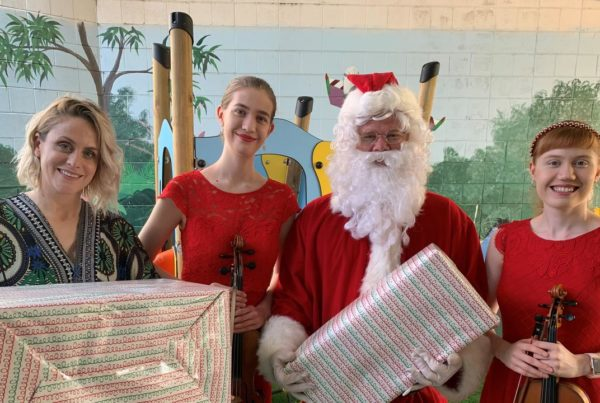Lisa donating toys with Santa