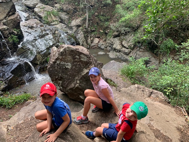Rory, Poppy and Louie smile at the camera sitting next to a waterfall