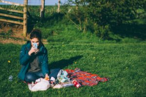 Woman using phone in a field on a picnic blanket