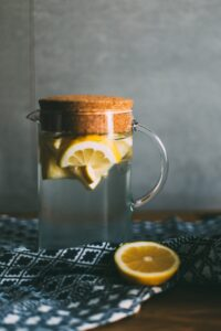 Glass jug filled with water and lemon slices with a cork lid